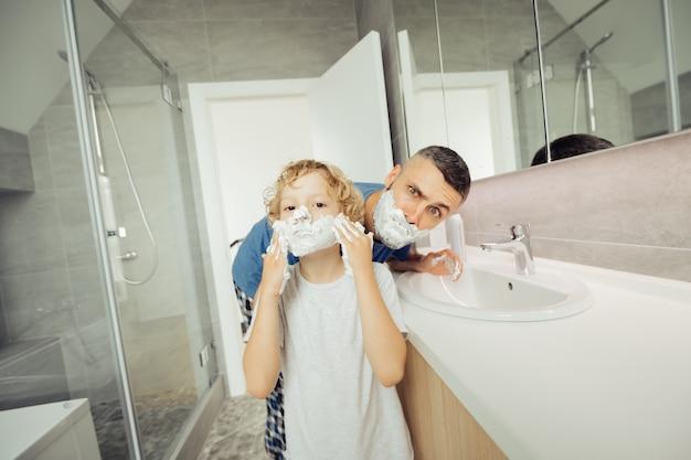 Miły, przyjemny chłopiec nakłada piankę do golenia na twarz