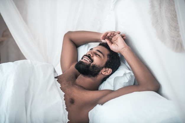 Miły sen. uśmiechnięty ciemnoskóry, brodaty mężczyzna z zamkniętymi oczami, leżący w białym łóżku w domu rano