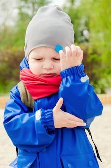 Miły słodki dwuletni chłopiec w niebieskiej kurtce i czerwonym szaliku uderzył go w łokieć. chłopiec ma wrzód