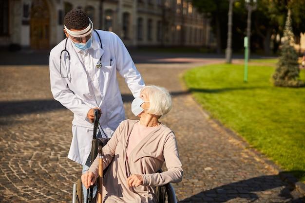 Miły specjalista medyczny w masce i osłonie twarzy patrzący na emeryta na wózku inwalidzkim