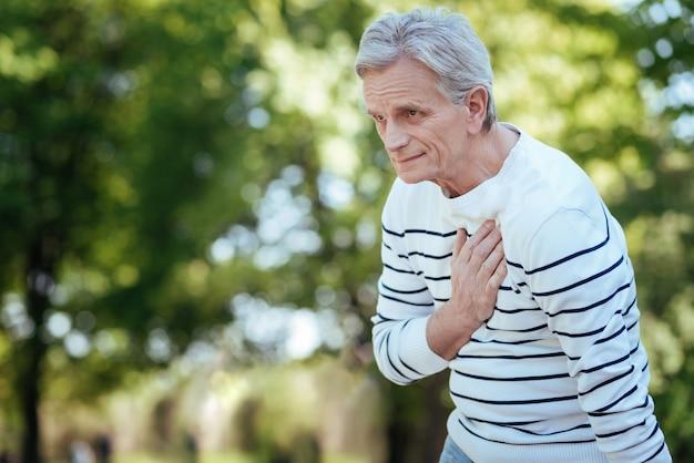 Miły, spokojny starszy mężczyzna stojący i cierpiący na ból w klatce piersiowej podczas spaceru po parku