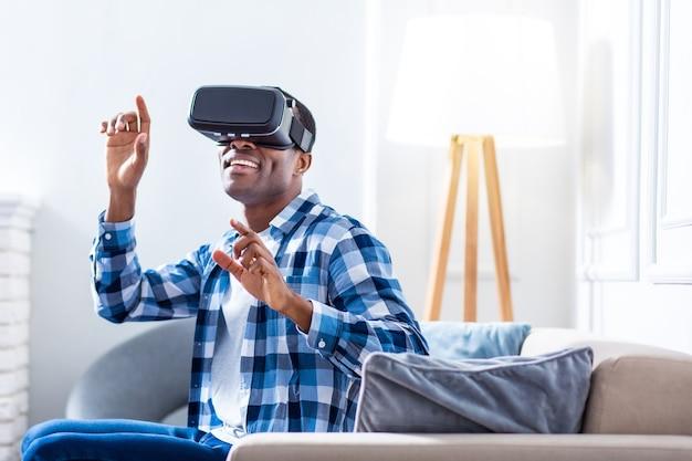 Miły, szczęśliwy dorosły mężczyzna siedzi na kanapie i doświadcza wirtualnej rzeczywistości podczas korzystania z okularów 3d