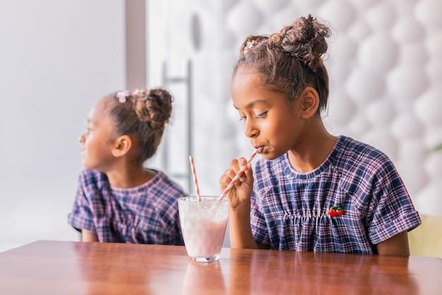 Miły weekend. urocza ciemnowłosa kręcona dziewczyna popija mleczny koktajl w miły weekend siedząc w stołówce z siostrą