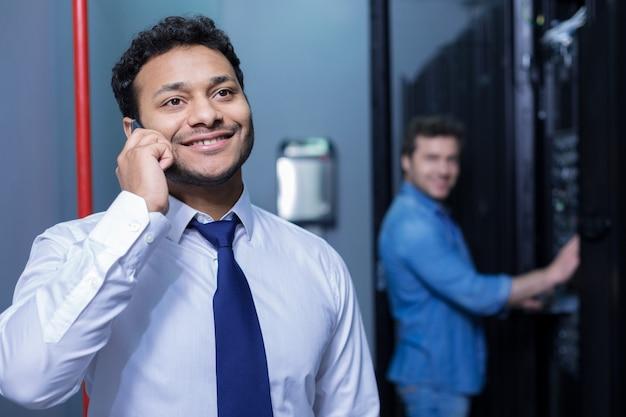 Miły, wesoły, pozytywny człowiek, uśmiechając się i rozmawiając przez telefon będąc w centrum danych