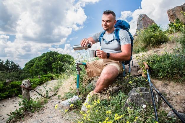 Miły, zachwycony mężczyzna z problemami fizycznymi, cieszący się swoją turystyczną trasą przy orzeźwiającej herbacie