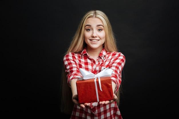 Miły zachwycony szczery nastolatek wyrażający szczęście i dając pudełko, stojąc odizolowany w czarnej ścianie