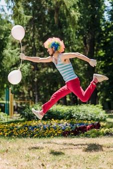 Mim skacze w parku z balonami.
