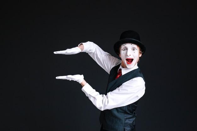 Mime trzyma dłonie równolegle w powietrzu