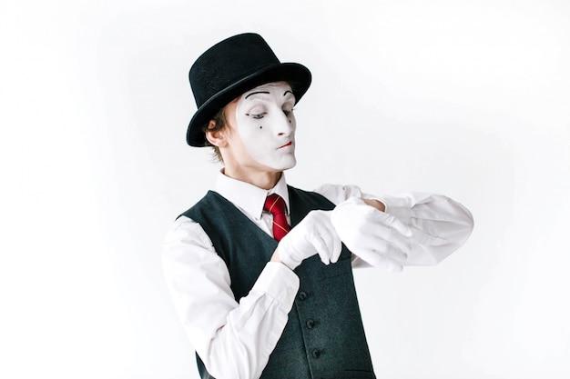Mime w czarnym kapeluszu i kamizelce patrzy na niewidzialny zegarek