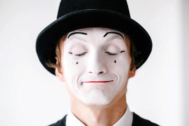Mime w czarnym kapeluszu stoi z zamkniętymi oczami