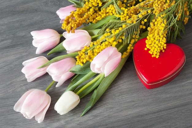 Mimoza i tulipany bukiet i serce w kształcie pudełka na szarym tle wwoden, zbliżenie