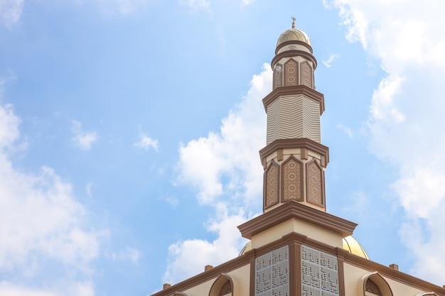 Minaret meczetu z niebieskim tłem nieba