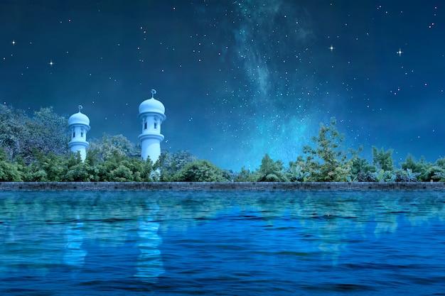 Minaret meczetu ze stawem i drzewami w nocy
