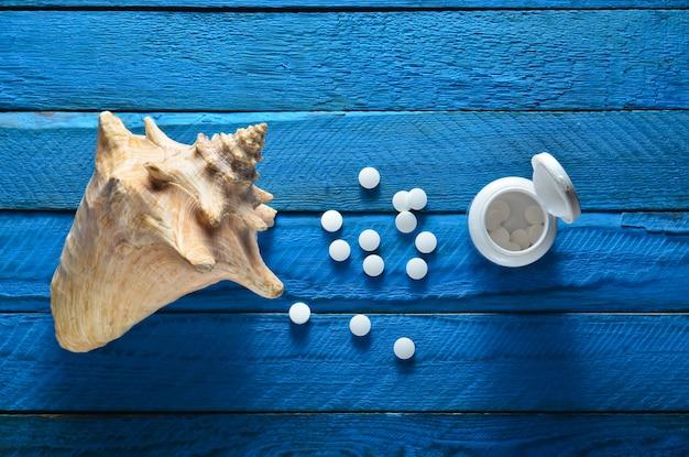 Minerały dla zdrowia i urody. tabletki wapnia, muszla na niebieskim drewnianym stole. widok z góry. pojęcie medyczne.