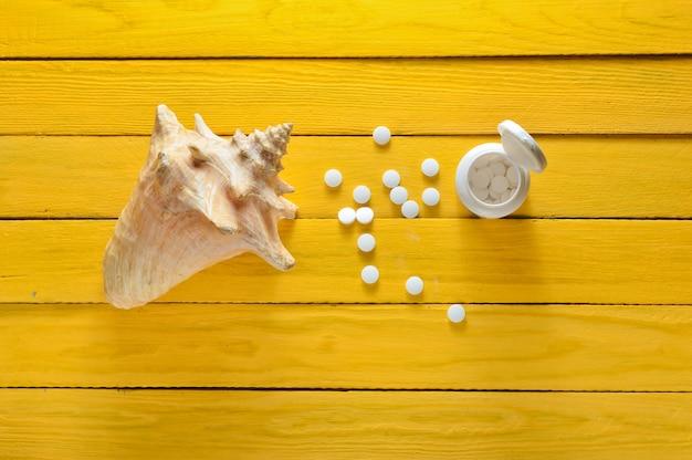 Minerały dla zdrowia i urody. tabletki wapnia, muszla na żółtym drewnianym stole. widok z góry. pojęcie medyczne.