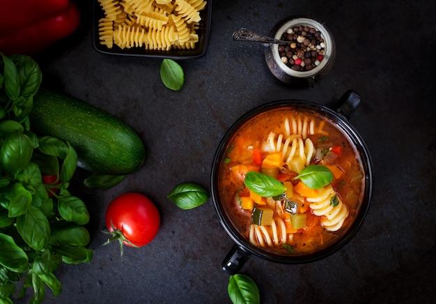 Minestrone, włoska zupa jarzynowa z makaronem na czarnym tle. widok z góry