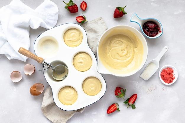 Mini babeczki truskawkowe na blasze do pieczenia na blacie kuchennym