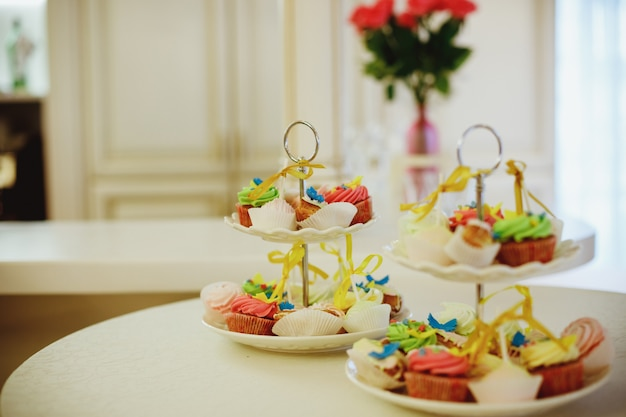 Mini babeczki waniliowe ozdobione cyjanowymi i różowymi koralikami cukierkowymi na przezroczystej, wielopoziomowej tacy na stole deserowym. słodki stół z owocami, herbatnikami. catering weselny. batonik na imprezie. pyszne babeczki