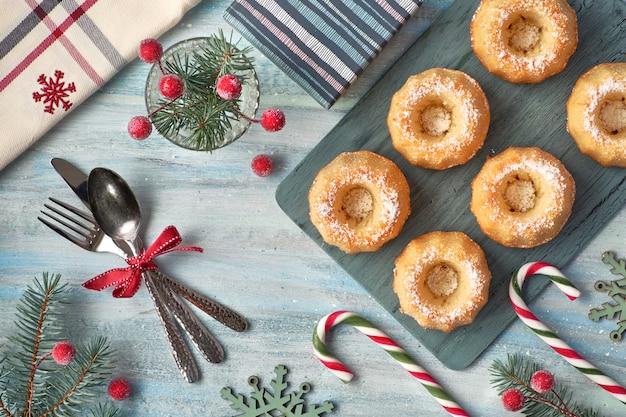 Mini babeczki z cukrem pudrem z gałązkami jodły, jagodami i laskami cukierków