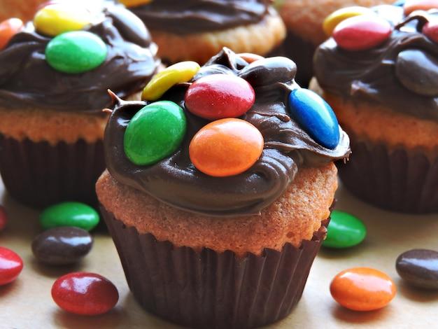 Mini babeczki z polewą z kremu czekoladowego i kolorowych słodyczy.