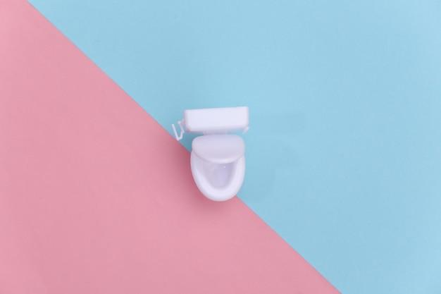Mini biała toaleta na różowym niebieskim tle. minimalizm. widok z góry