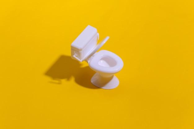 Mini biała toaleta na żółtym tle z głębokim cieniem. minimalizm.