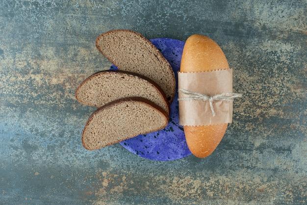 Mini biały chleb z kromkami świeżego ciemnego chleba na niebieskim talerzu