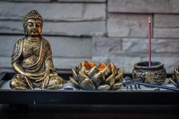 Mini, biurko zen ogród z zapaloną świecą i mały budda w nim.