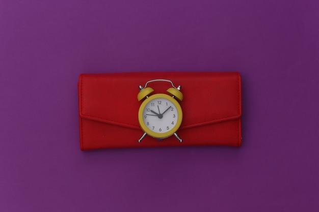 Mini budzik i czerwony portfel na fioletowym tle.