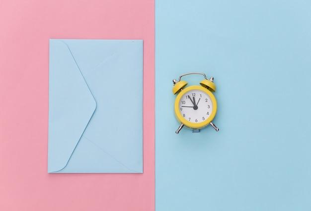 Mini budzik i koperta na różowym niebieskim tle pastelowych.