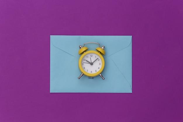 Mini budzik i koperty na fioletowym tle.
