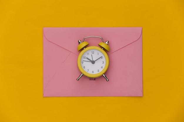 Mini budzik i koperty na żółtym tle.