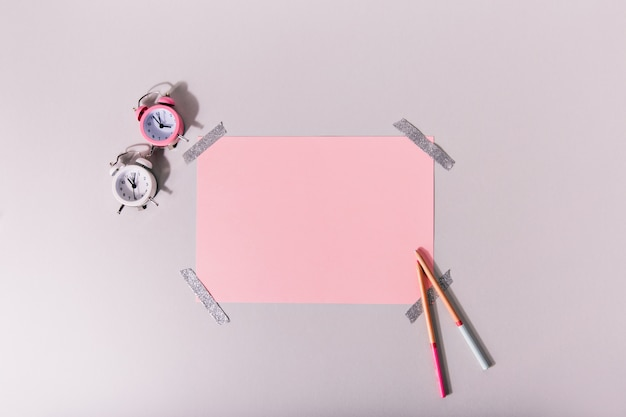 Mini budzik obok zestawu różowej papeterii