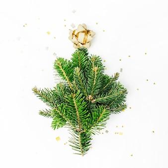 Mini choinka wykonana z gałęzi jodłowej ze złotą kokardką. koncepcja wakacje i uroczystości. płaski układanie, widok z góry