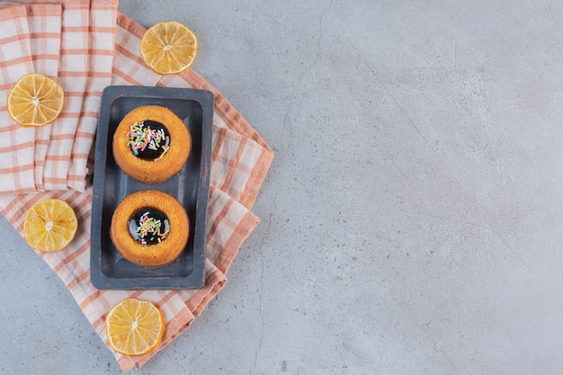 Mini ciastka z galaretką i plasterkami owoców na kamiennym stole.