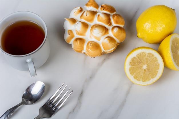 Mini ciasto cytrynowe, cytryny i filiżanka herbaty.
