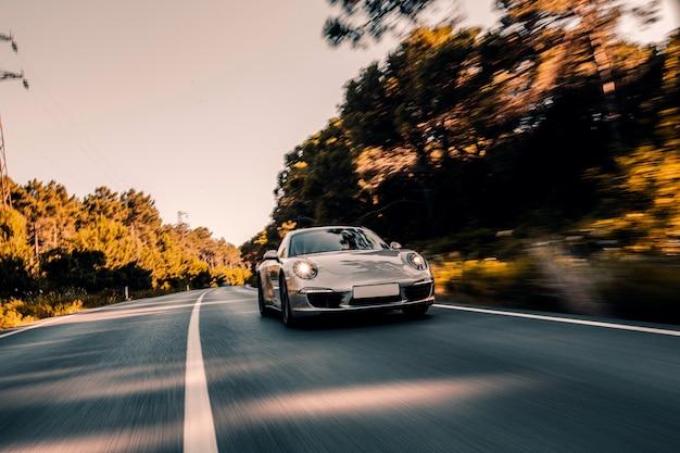 Mini coupe na drodze z włączonymi światłami przednimi.