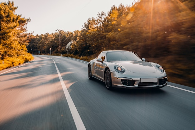 Mini coupe w kolorze srebrnym na drodze. jedź pod słońcem.