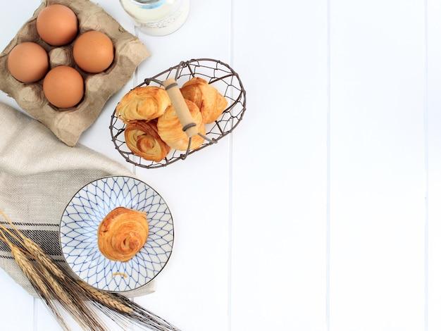 Mini croissant z mlekiem, ciasto kruche z masłem z francji. serwowane na talerzu i tkanym koszu drucianym na białej kuchni. skopiuj miejsce na tekst.