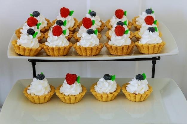 Mini deserowe tarty owocowe na dwupoziomowej podstawce. produkt piekarniczy.