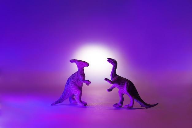 Mini dinozaury w neonowo różowym i niebieskim kolorze.