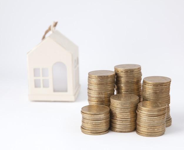 Mini dom na stosie monet. pojęcie nieruchomości inwestycyjnej. mieszkanie na kredyt
