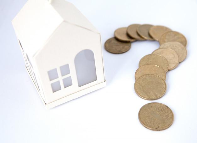 Mini dom na stosie monet. pojęcie nieruchomości inwestycyjnej