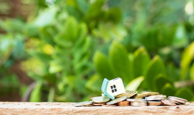 Mini dom zbankrutował na stosie monet. pojęcie nieruchomości inwestycyjnej.