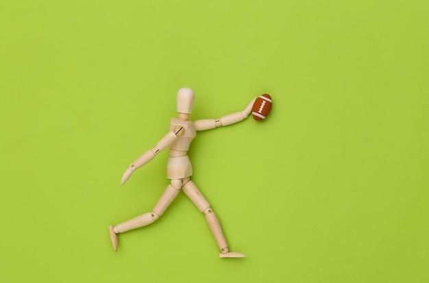 Mini drewniana lalka biegnie z piłką do rugby na zielonym tle
