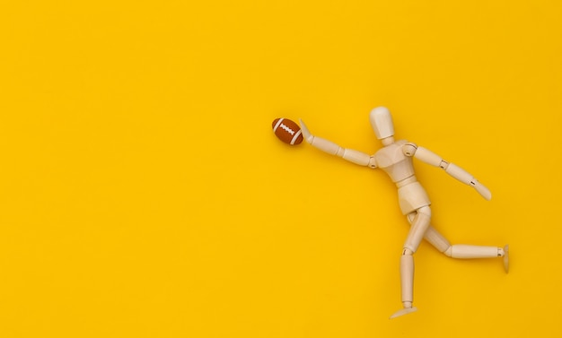 Mini drewniana lalka biegnie z piłką do rugby na żółtym tle