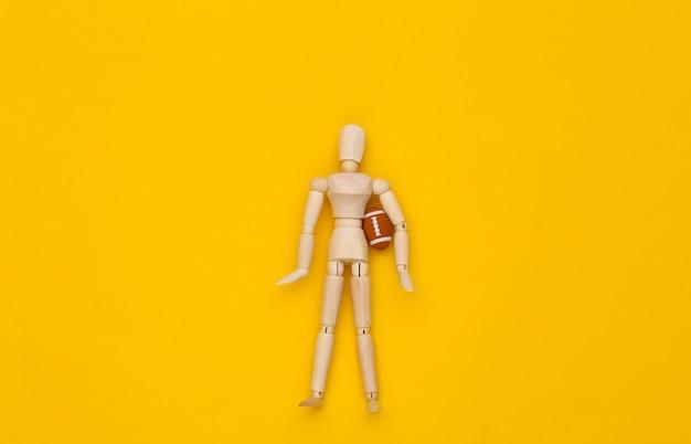 Mini drewniana lalka trzymająca piłkę do rugby na żółtym tle