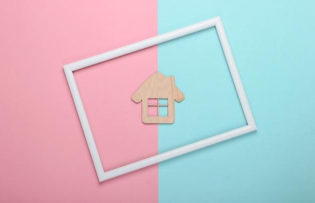 Mini drewniany domek na różowo-niebieskiej pastelowej powierzchni z białą ramą