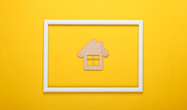 Mini drewniany domek na żółtej powierzchni z białą ramą