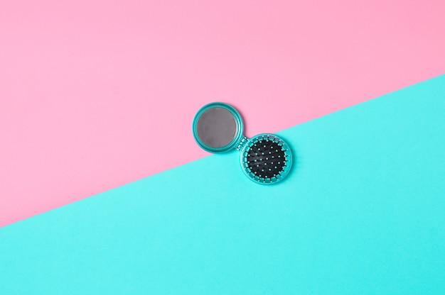 Mini grzebień-lustro na wielobarwnej pastelowej powierzchni. widok z góry. moda lat 90